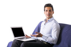 Young man showing laptop computer sitting on couch. Pure white background stock photography