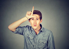 Young man showing loser sign on forehead, looking with disgust. Isolated on gray background. Negative human emotion facial expression feeling Royalty Free Stock Images