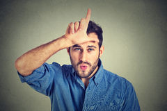 Young man showing loser sign on forehead, looking at you with disgust. Closeup portrait of serious young man showing loser sign on forehead, looking at you with Royalty Free Stock Photo