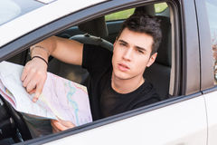 Young Man showing map inside of a car Stock Image