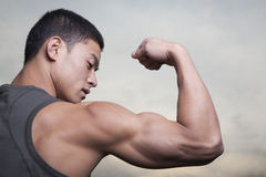 Young Man showing off his bicep muscles Royalty Free Stock Photos