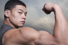 Young Man showing off his bicep muscles Stock Image