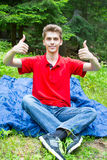 Young man showing Ok sign. Over green nature background Stock Photography