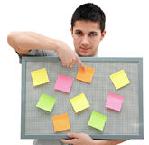 Young man showing onto the reminder board. A handsome young man holding a reminder board with plenty of colorful post-it on it Stock Photo