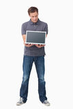 Young man showing screen of his laptop Stock Image