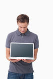 Young man showing screen of his notebook Royalty Free Stock Image