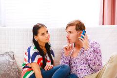 Young man showing shh... gesture to girlfriend Royalty Free Stock Photo