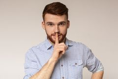 Young man showing silence sign and putting finger to lips. Do not speak. Young man showing silence sign and putting finger to lips on studio background, panorama stock images