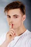 Young man showing silent gesture. Royalty Free Stock Images