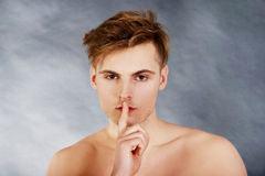 Young man showing silent gesture. Stock Photos