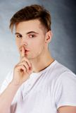 Young man showing silent gesture. Royalty Free Stock Image