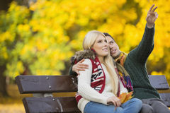 Young man showing something to woman while gesturing in park during autumn Stock Photography