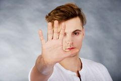 Young man showing stop sign. Stock Photography