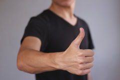 Young man showing thumb up. Isolated on gray background. Young man in black t shirt shows thumb up. Isolated on gray background Stock Photography