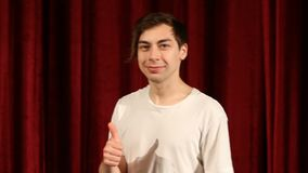 Young man showing thumb up on red curtain background.  stock footage