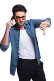Young man showing the thumbs down gesture Stock Image
