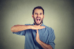 Young man showing time out hand gesture, frustrated screaming to stop Royalty Free Stock Image