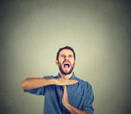 Young man showing time out hand gesture, frustrated screaming to stop Stock Images