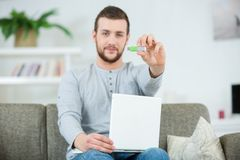 Young man showing usb. Young man showing a usb stock photo