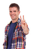 Young man showing victory sign. Handsome casual young man showing victory sign, isolated on white background Royalty Free Stock Images