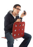 Young man shows cellphone sitting on stool Royalty Free Stock Images