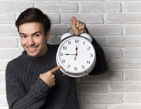 Young Man Shows on Clock. Young Man Holding Big Clock stock photos