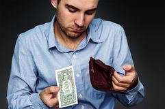 A young man shows that he has in the wallet a one dollar stock photos