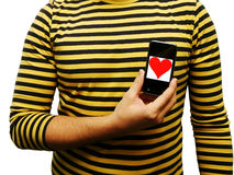 Young man shows heart on mobile phone. Royalty Free Stock Image