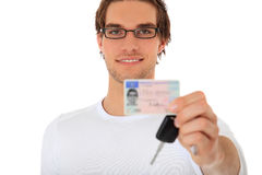 Young man shows his drivers license and car keys. Proud young man showing his drivers license and car keys. All on white background royalty free stock photo