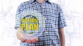Young man shows a hologram of the planet Earth and text Action plan stock video