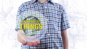 Young man shows a hologram of the planet Earth and text Internet of things. Boy with future technology 3d projection on a modern white digital background stock video footage