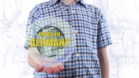 Young man shows a hologram of the planet Earth and text Made in Germany. Boy with future technology 3d projection on a modern white digital background stock footage