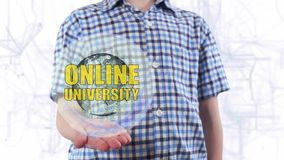 Young man shows a hologram of the planet Earth and text Online university. Boy with future technology 3d projection on a modern white digital background stock footage