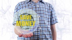 Young man shows a hologram of the planet Earth and text Save money. Boy with future technology 3d projection on a modern white digital background stock video footage