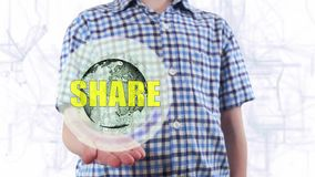 Young man shows a hologram of the planet Earth and text Share. Boy with future technology 3d projection on a modern white digital background stock video