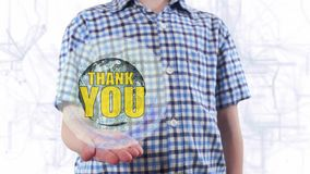 Young man shows a hologram of the planet Earth and text Thank you. Boy with future technology 3d projection on a modern white digital background stock video footage