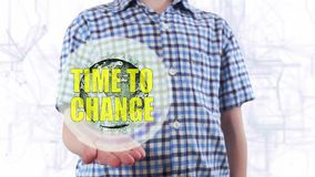 Young man shows a hologram of the planet Earth and text Time to change