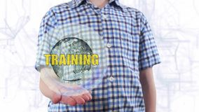 Young man shows a hologram of the planet Earth and text Training. Boy with future technology 3d projection on a modern white digital background stock video