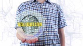 Young man shows a hologram of the planet Earth and text Vacation. Boy with future technology 3d projection on a modern white digital background stock footage