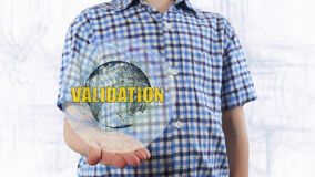 Young man shows a hologram of the planet Earth and text Vacation royalty free stock photography