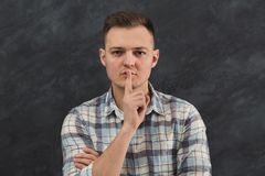 Young man shows hush be quiet. Handsome guy holding finger at his lips, gray studio background, copy space. Secret, privacy concept Royalty Free Stock Images