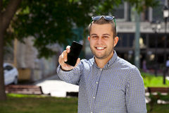 A young man shows a mobile phone screen Stock Images