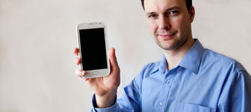 Young man shows smart phone in the right hand. Against the gray background royalty free stock image