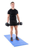 Young man shows starting position of biceps curl Royalty Free Stock Image