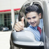 Young man shows thumb up in the car Stock Image