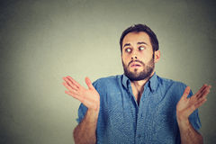 Young man shrugging shoulders who cares so what I don't know. Closeup portrait young man shrugging shoulders who cares so what I don't know gesture on grey wall stock images