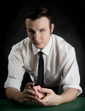 A young man shuffles a deck of cards. At a casino table Royalty Free Stock Images