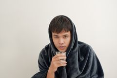 A young man is sick with flu, lies at home under a blanket, takes a pill stock photo