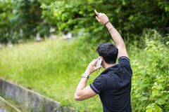 Young man on side of a road, calling and waiting Royalty Free Stock Photos