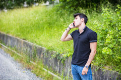 Young man on side of a road, calling and waiting Stock Photos